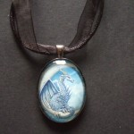 Wish Dragon Picture Pendant shows a rare blue dragon sitting on a starry crescent moon