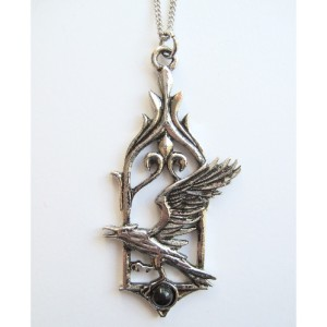 The Raven Pendant shows a raven upon a black stone set into a Gothic window