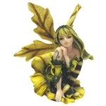 Patchouli Fairy Figurine sitting inside a yellow flower she is dressed in green and yellow
